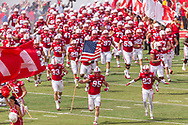 Jack Gangwish #95 of the Nebraska Cornhuskers carries the American flag and leads the Nebraska on the field prior to Nebraska's 33-28 loss to BYU on Sept. 5, 2015. Photo by Aaron Babcock