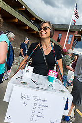 August 22, 2017 - Truckee, California, U.S - Truckee resident, SILKE PFLUEGER, encourages others in attendance at the Truckee Tahoe Airport to write postcards to their elected leaders. PFLUEGER is one of approximately 50-60 protesters waiting for an opportunity to talk with California's 4th district Congressman, Tom McClintock, before he attends a private meeting with the Contractors Association of Truckee Tahoe (CATT) at the Truckee Tahoe Airport in Truckee, California, on Tuesday, August 22, 2017. According to several local-area residents/constituents in attendance, they've requested a town hall meeting with McClintock for approximately two years without luck. Protester Paco Lindsay said that their protest was ''in no way a reflection at all on CATT. (Credit Image: © Tracy Barbutes via ZUMA Wire)