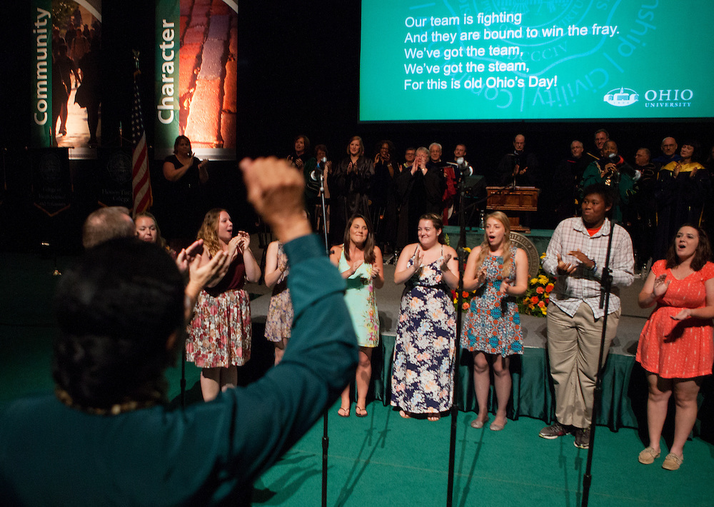 Audience members cheer as the Ohio University Women's Chorale, Title IX, performs the university fight song during the New Student Convocation on Aug. 24, 2014. Photo by Lauren Pond