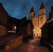 West facade of the Abbatiale Sainte-Foy de Conques or Abbey-church of Saint-Foy at night, Conques, Aveyron, Midi-Pyrenees, France, a Romanesque abbey church begun 1050 under abbot Odolric to house the remains of St Foy, a 4th century female martyr. An arched portico surrounds the doors, above which is a carved tympanum. The church is on the pilgrimage route to Santiago da Compostela, and is listed as a historic monument and a UNESCO World Heritage Site. Picture by Manuel Cohen