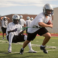 Christian Coffey, left, and Noah Vickers work together on a drill during Patriots football practice at Miyamura High School in Gallup Monday.