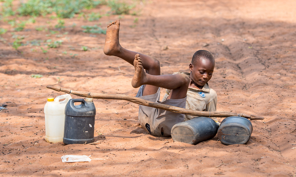 Young Zambian boy trips over himself as he attempts tp set down jugs of water, Mukuni Village, Zambia