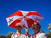 "11 NOVEMBER 2013 - PHOENIX, AZ: Women under a parasol watch the Phoenix Veterans Day Parade. The Phoenix Veterans Day Parade is one of the largest in the United States. Thousands of people line the 3.5 mile parade route and more than 85 units participate in the parade. The theme of this year's parade is ""saluting America's veterans.""     PHOTO BY JACK KURTZ"