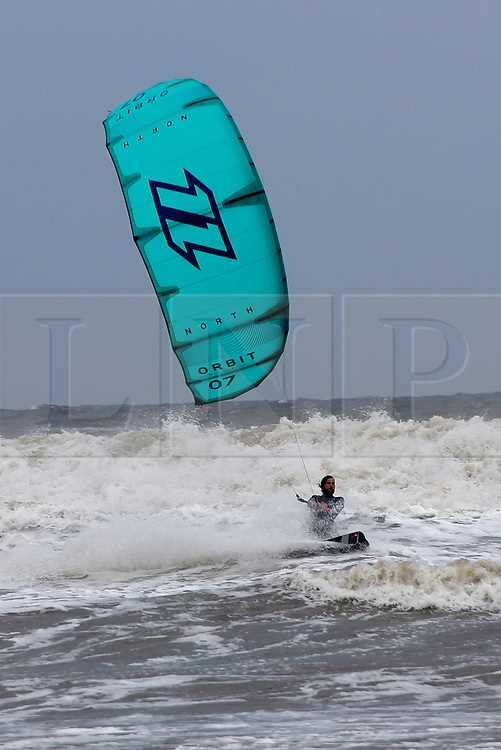 © Licensed to London News Pictures. 04/10/2019. Porthcawl, Bridgend, Wales, UK. Kite surfers take to the water at Rest Bay near Porthcawl in Bridgend as Storm Lorenzo, named after ex-hurricane Lorenzo, by Met Éireann, hits the Welsh seaside resort of Porthcawl in Bridgend, UK. Photo credit: Graham M. Lawrence/LNP