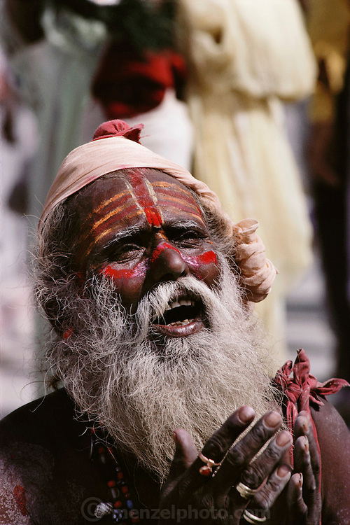 Portrait of a holy man praying at Kumbh Mela.  Every 12 years, millions of devout Hindus celebrate the month-long festival of Kumbh Mela by bathing in the holy waters of the Ganges at Hardiwar, India. Hundreds of ashrams set up dusty, sprawling camps that stretch for miles. Under the watchful eye of police and lifeguards, the faithful throng to bathe in the river.
