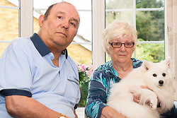 Annette and Raymond Timmins in their home with their Japanese Spitz Poppet They have have forked out thousands on a fierce 11-year battle with the owner of a neighbouring property - over a 76cm strip of land in a car park near their homes.. Maidenhead, September 12 2018.