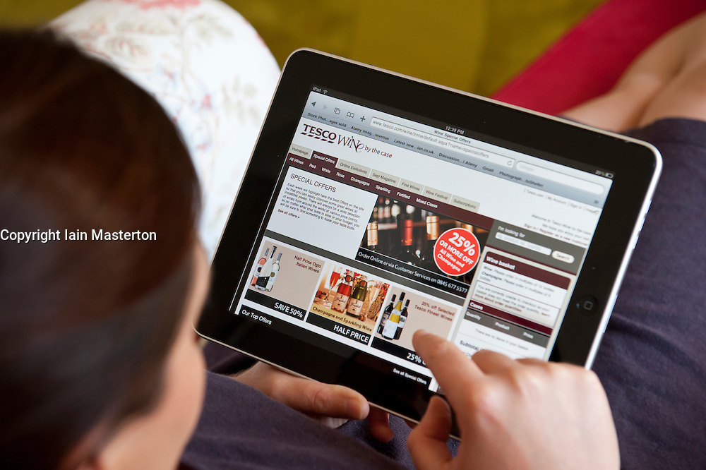 Woman shopping online for wine at UK retailer Tesco website on an iPad tablet computer