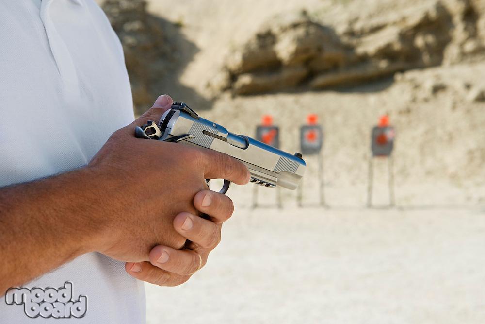 Man holding hand gun at firing range, mid section, close-up