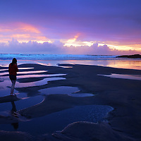 Dramatic sunset in Cornwall, England with female teenage figure