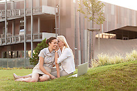Young businesswoman whispering to female colleague on office lawn