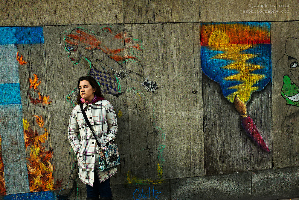 Woman standing in front of chalk art on building wall, New York, NY, US