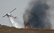 July 13, 2015 - Yorba Linda, CA, USA - <br /> <br /> water planes take to the sky to help put out fires<br /> <br /> A helicopter drops water on vegetation along the 241 toll road on the Irvine / Orange border Monday. More than 150 acres burned and threatened some structures near Irvine Lake causing officials to close down Santiago Canyon Road in unincorporated Orange County, California <br /> ©Exclusivepix Media