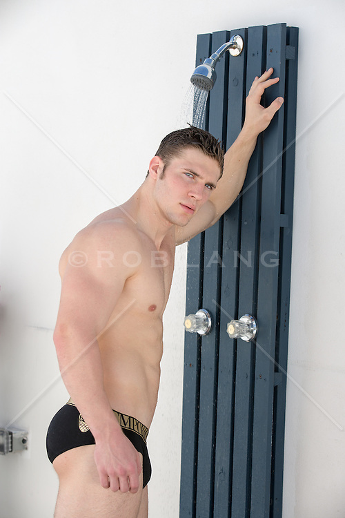 sexy man in an outdoor shower by the beach