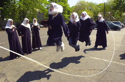 "Students from the Al-Ghazaly Muslim School in New Jersey do a ""triple jump""  during recess.  <br /> © Danielle P. Richards / Jersey Girl Stock Images<br /> <br /> Keywords: Muslim, diversity, friendship, youth, jumping rope, melting pot, minorities, play, Arab, cultural awareness, exercise, school, fun, multicultural, recess, hijab"