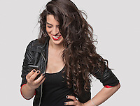 Happy young female using cell phone against gray background