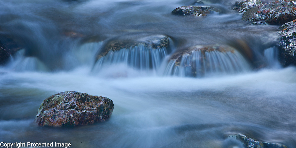 Clear streaming water is softened via a long aperture setting, somewhere in Olympic National Park in Washington.