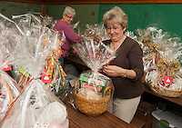 Sue Laramie and Marie Leahy attach bows for the finishing touch on theme baskets for the annual Nutcracker Christmas Fair held November 7th - 8th at Sainte Andre Bassette Parish.  (Karen Bobotas/for the Laconia Daily Sun)