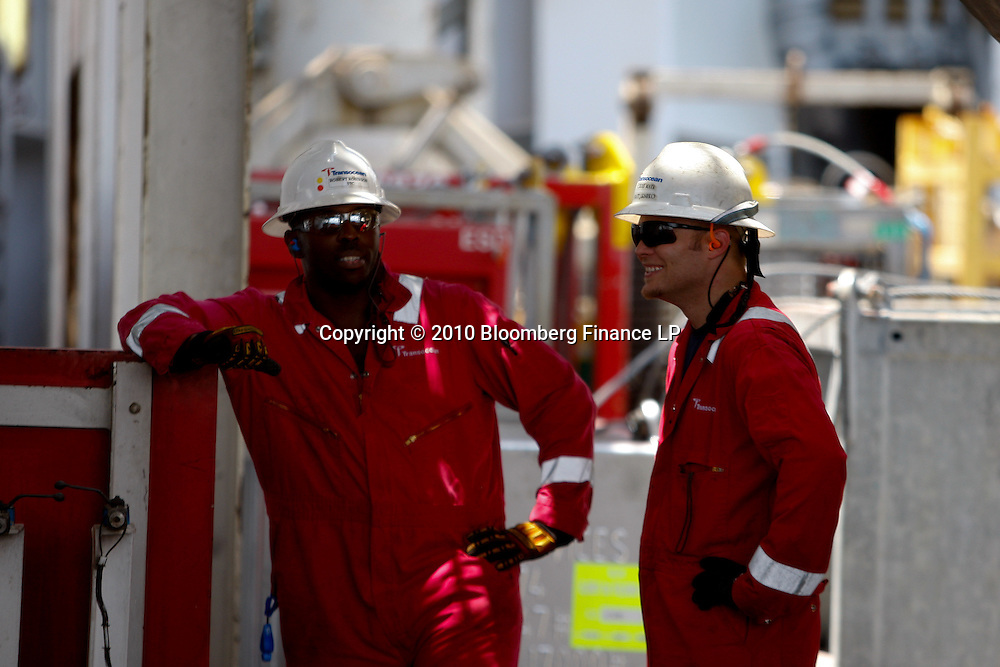 Transocean workers talk on board the Transocean Development Driller II rig leased by BP Plc which is drilling a backup relief well at the BP Plc Macondo well site in the Gulf of Mexico off the coast of Louisiana, U.S., on Saturday, August 7, 2010. BP successfully used the 'static kill', procedure  pumping mud into the top of the damaged well, BP plans now to finish a relief well to permanently plug the well by mid-August. Photographer: Derick E. Hingle/Bloomberg