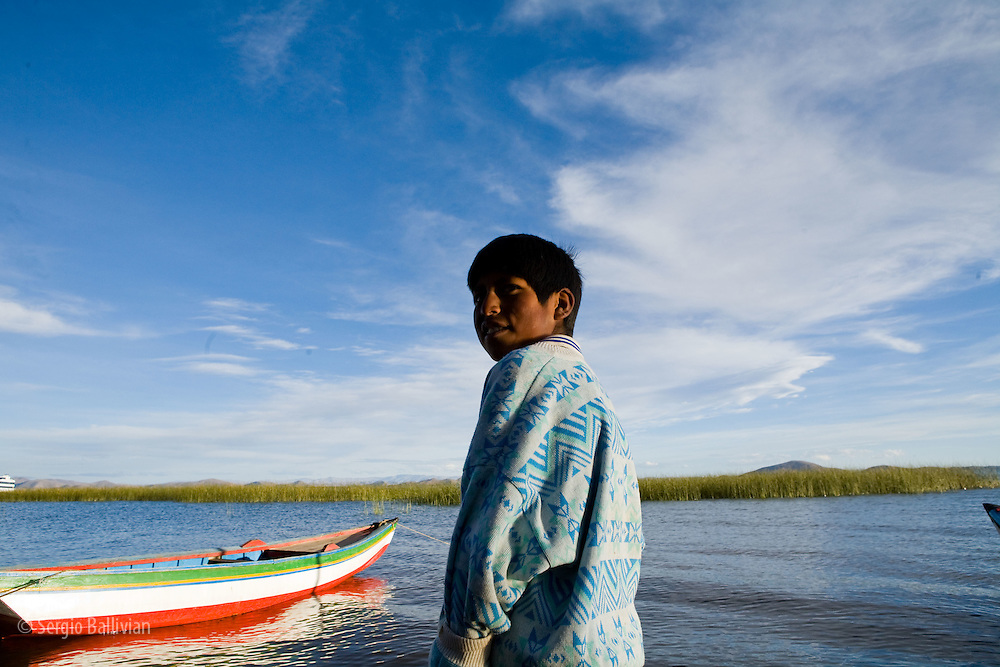 A young Aymara Indian kid smiles next to his fishing boat on Lake Titicaca in Bolivia.