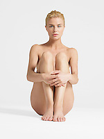 Nude Young Woman sitting with hands on knees portrait