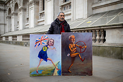 © Licensed to London News Pictures. 15/01/2019. London, UK. Satirical artist Kaya Mar poses with his paintings of Theresa May and Jeremy Corbyn. Today, MPs are due to vote on British Prime Minister Theresa May's EU withdrawal deal, after the previous vote in December was postponed. Photo credit : Tom Nicholson/LNP