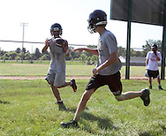 Nick Strait, 17, senior, looks the ball into his hands during a drill on the first day of football practice at Central City High School in Central City on Wednesday afternoon, August 3, 2011.