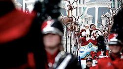 Mr. and Mrs. Santa are seen clearly enjoying the attention they get as they ride up the Parkway in a sled pulled by Dasher, Dancer, Prancer, Vixen, Comet, Cupid, Donner, and Blitzen. (Bas Slabbers/for NewsWorks)