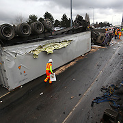 Crews work the scene after a semi truck hauling eggs was involved in an accident and drove off Interstate 5 onto the Ravenna on-ramp below.  Four people were injured in the accident and the truck's fuel tanks ruptured, spilling diesel on the roadway below. (Joshua Trujillo, seattlepi.com)