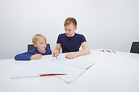 Mid adult father assisting boy in studies