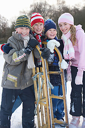 Group of smiling children leaning on a sled