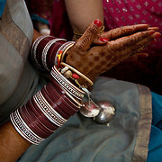 New Delhi, India, January 21, 2011. Sumedha and Sapan Wedding. Propitiatory celebrations for the bride. Sumedha wears a series of bangles, as one of the most important symbols of the marriage union. According to tradition, the bracelets should be worn for a year.