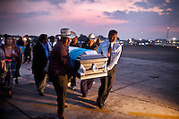 Funeral directors and family members carry the caskets containing the bodies of victims killed by drug cartels, at an Air Force base in Guatemala City, Wednesday, March 21, 2012. The remains of 11 Guatemalan citizens were repatriated from Mexico on Wednesday. 193 bodies found in the northern Mexican state of Tamaulipas, in 26 mass graves in April 2011. Mexican authorities believe the dead were mostly migrants kidnapped from buses and killed by the Zetas drug cartel.