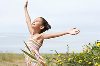 Pre-teen girl standing beside flowers eyes closed arms outstretched side view