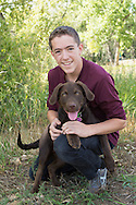 Fun senior picture with chocolate labrador puppy, Niwot