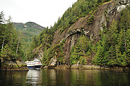 A small cruise ship sails through a narrow, cliff lined passage in Misty Fjords National Monument, Alaska.