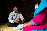 Rahidul Islam (left) interviewing a garment worker called Kohinur (right) in her home in Dhaka, Bangladesh. <br /> <br /> Rahidul works for the BRAC microfinance, financial diaries project. This programme works to improve the financial literacy of garment workers.