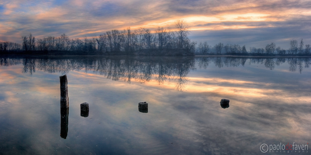 A moody view at dawn of the Po River nearby Carignano in Piedmont, italy. With some beautiful reflections in the still waters.