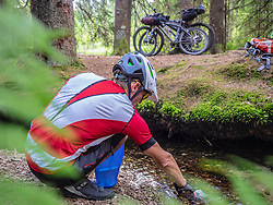 Mountain biker resting by the river stream in the Black forest, Baden-Wuerttemberg, Germany