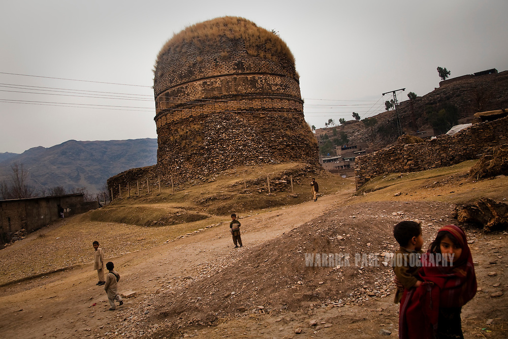 Village children play next to the Shingardar Stupa in the Swat Valley, on February 11, 2011, in Gumbatuna, Pakistan. The Kingdom of Gandhara lasted from early 1st millennium BC to the 11th century AD, and was located in northern Pakistan and eastern Afghanistan. (Photo by Warrick Page)