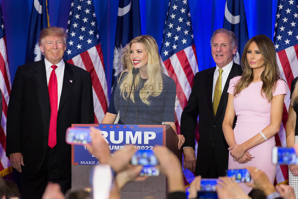 Billionaire and GOP presidential candidate Donald Trump smiles as daughter Ivanka Trump addresses supporters during victory celebrations following their win in the South Carolina Republican primary February 20, 2016 in Spartanburg, South Carolina, USA .