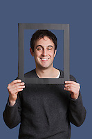 Portrait of young man smiling through frame over blue background