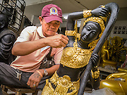 """12 NOVEMBER 2012 - BANGKOK, THAILAND:   A man finishes a statue of Shiva at a workshop Bamrung Muang Street in Bangkok. Although Hindu, Shiva also figures prominently in Thai Buddhism. Thanon Bamrung Muang (Thanon is Thai for Road or Street) is Bangkok's """"Street of Many Buddhas."""" Like many ancient cities, Bangkok was once a city of artisan's neighborhoods and Bamrung Muang Road, near Bangkok's present day city hall, was once the street where all the country's Buddha statues were made. Now they made in factories on the edge of Bangkok, but Bamrung Muang Road is still where the statues are sold. Once an elephant trail, it was one of the first streets paved in Bangkok. It is the largest center of Buddhist supplies in Thailand. Not just statues but also monk's robes, candles, alms bowls, and pre-configured alms baskets are for sale along both sides of the street.    PHOTO BY JACK KURTZ"""