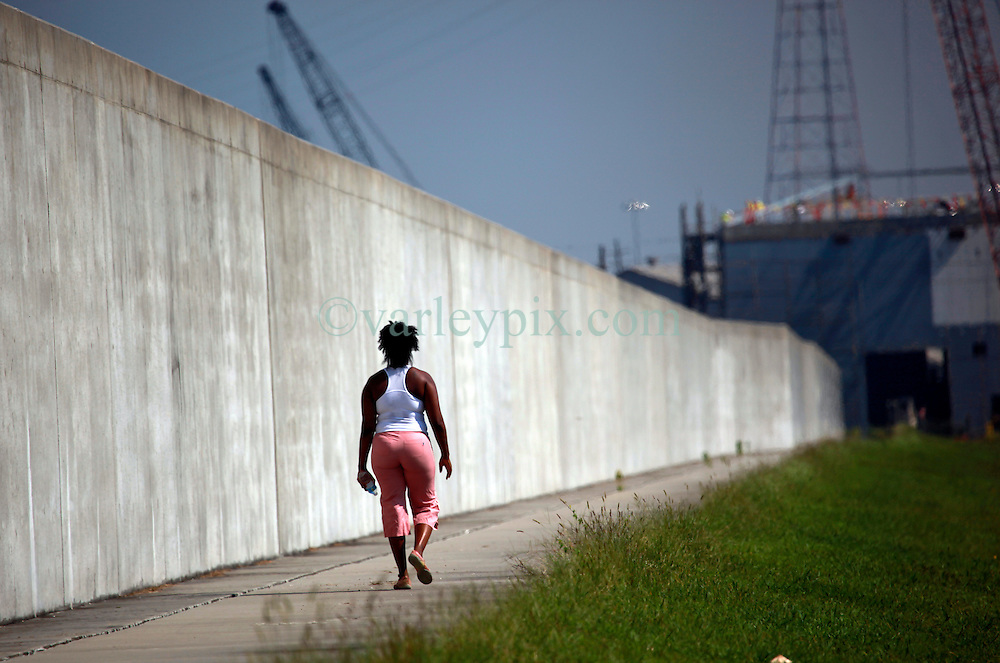 29 August 2013. Lower 9th Ward, New Orleans, Louisiana.<br /> Hurricane Katrina memorial 8 years later. <br /> A local resident walks along the levee in the Lower 9th ward, quietly remembering those who perished in the storm 8 years ago.<br /> Photo; Charlie Varley