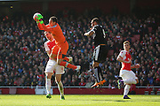 Arsenal goalkeeper, David Ospina (13) claiming in front of Watford striker, Troy Deeney (9) during the The FA Cup Quarter Final match between Arsenal and Watford at the Emirates Stadium, London, England on 13 March 2016. Photo by Matthew Redman.