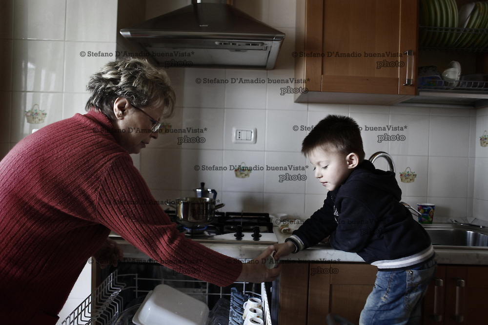 Nonna insegna giocando a suo nipote come fare la lavastoviglie.<br />