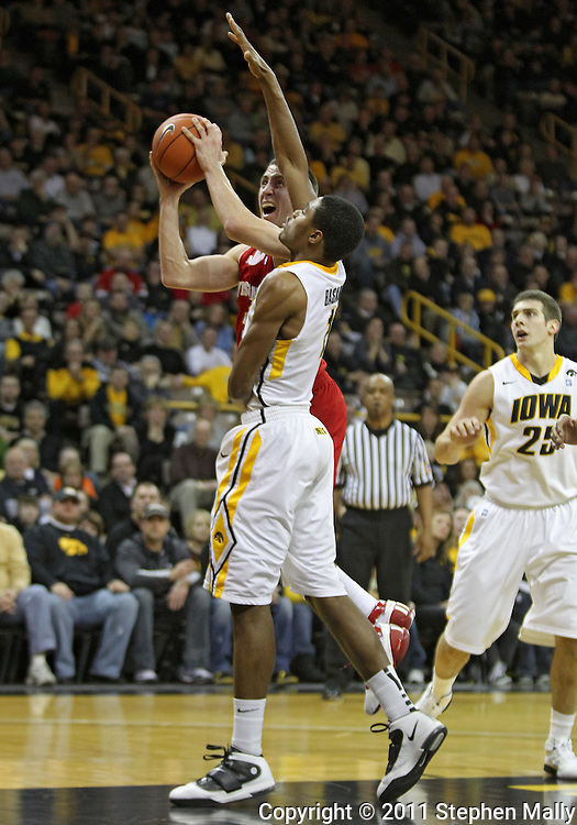 February 09 2011: Wisconsin Badgers guard Josh Gasser (21) puts up a shot as Iowa Hawkeyes forward Melsahn Basabe (1) defends during the first half of an NCAA college basketball game at Carver-Hawkeye Arena in Iowa City, Iowa on February 9, 2011. Wisconsin defeated Iowa 62-59.