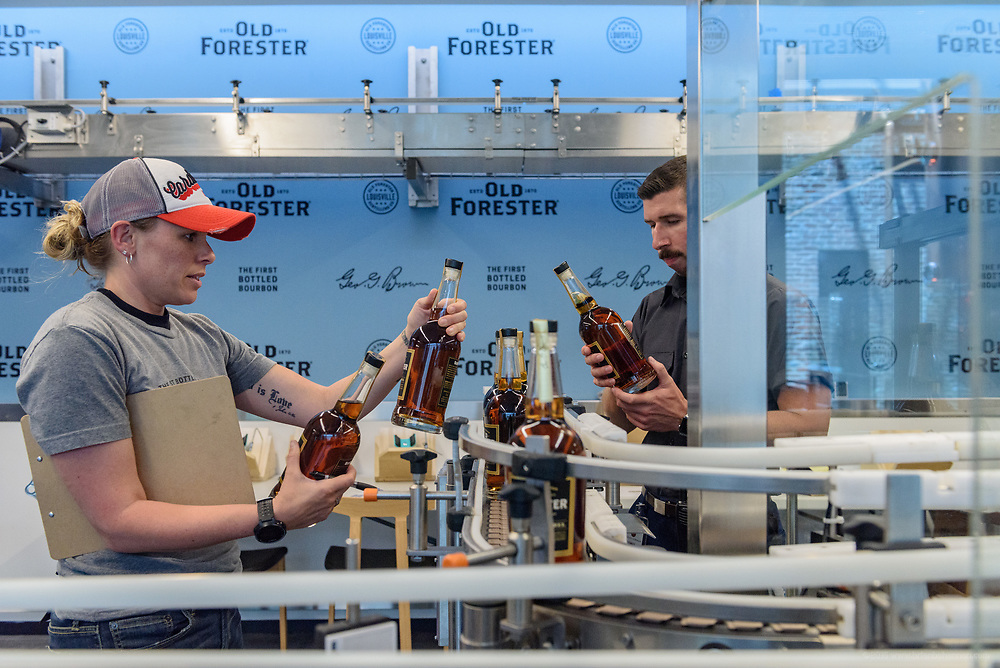 Maria Lewis and Caleb Piper make sure the labels line up and everything is on point in the bottling area of the Old Forester Distilling Company on Whisky Row in Louisville, Ky. June 6, 2018
