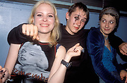 A teenager wearing eye make up, with his arms around two girls, at a party, bar, UK 2004