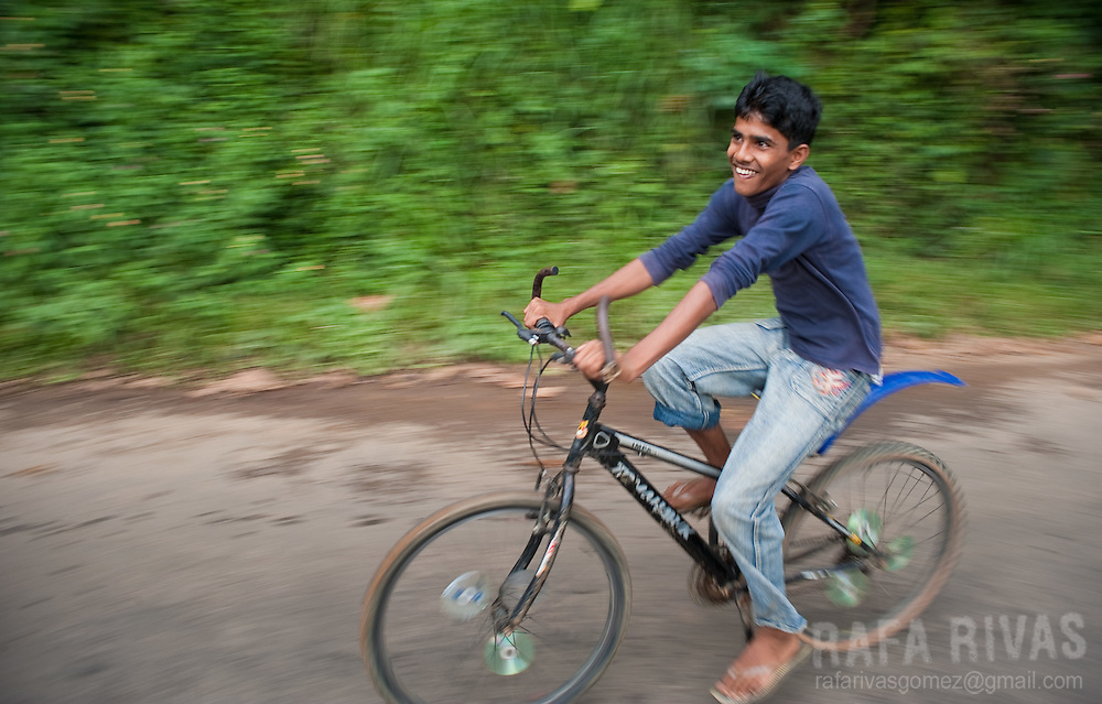 A boy smiles as he rides a bicycle in a jungle area close to Rakwana, Sri Lanka, on February 28, 2011. Photo Rafa Rivas
