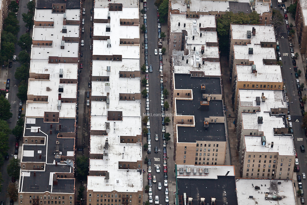 741 Lydig St, The Bronx, NY 10462, 40.854665,-73.866043, Apartment buildings in repeating shapes line the streets of the Bronx in New York. The large surface area of the rooftop shows opportunity for habitable outdoor roof spaces as well as the contributions of these surfaces, if left untreated, to the heat island effect in urban areas.